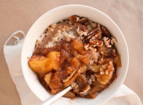 bowl of oatmeal topped with homemade cinnamon applesauce and pecans