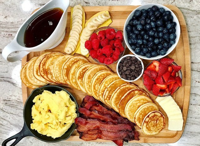 pancake board with berries chocolate chips syrup eggs bacon