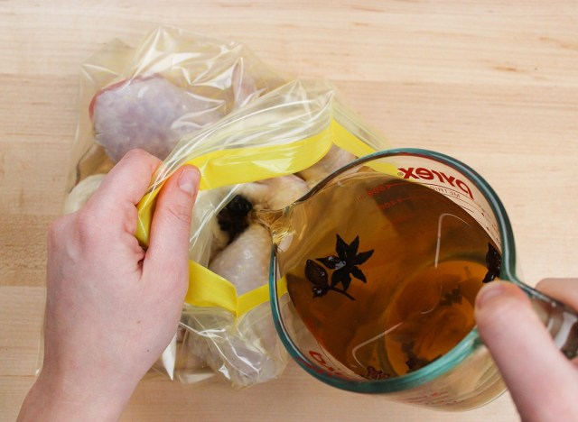 pouring wet brine into bagged uncooked chicken
