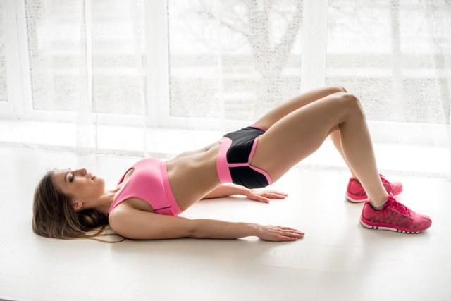 Fitness athlete performs an exercise bridge in the studio