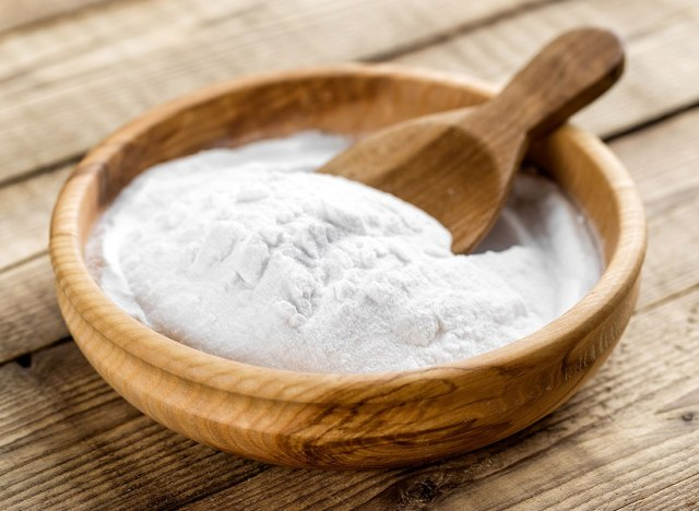 Baking soda in wooden bowl with wooden spoon