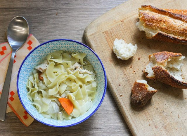 Crock pot chicken noodle soup with bread on a table.