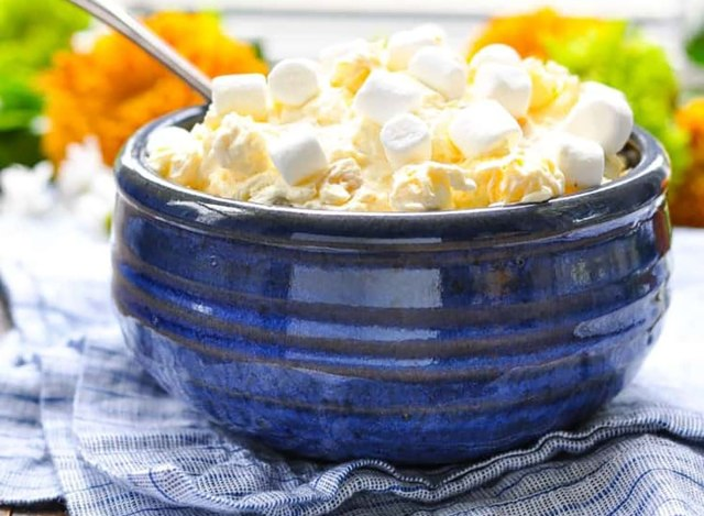 pineapple orange fluff salad topped with marshmallows in blue bowl