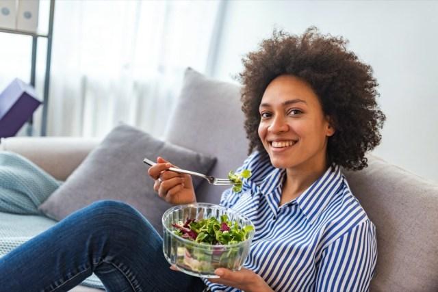 american woman eating vegetable salad at home