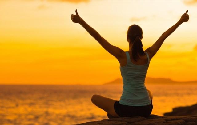 woman celebrating during a beautiful sunset