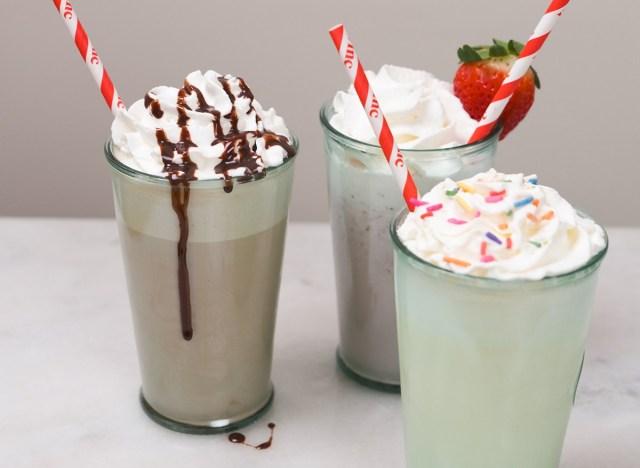 three types of milkshakes with red straws