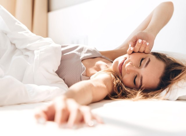 Woman waking up from a restful nights sleep in her bed