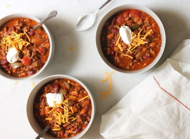 wendy's copycat chili in three bowls on a marble counter with cheese and sour cream