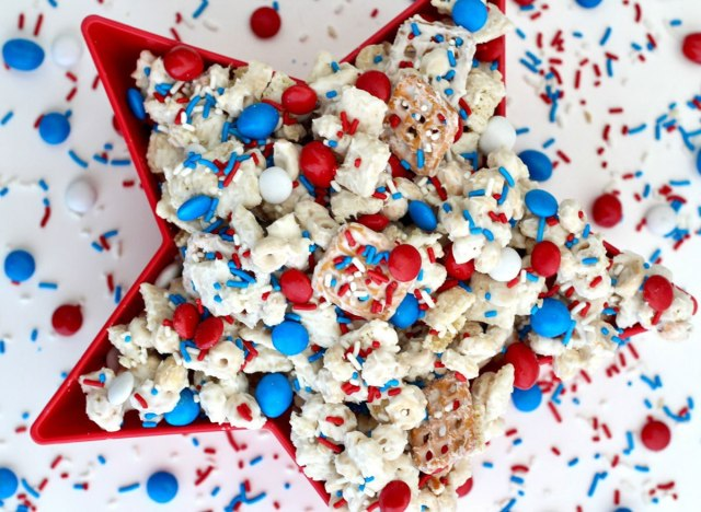 chex mix with red white and blue m&ms and sprinkles in red star bowl with sprinkles on white background