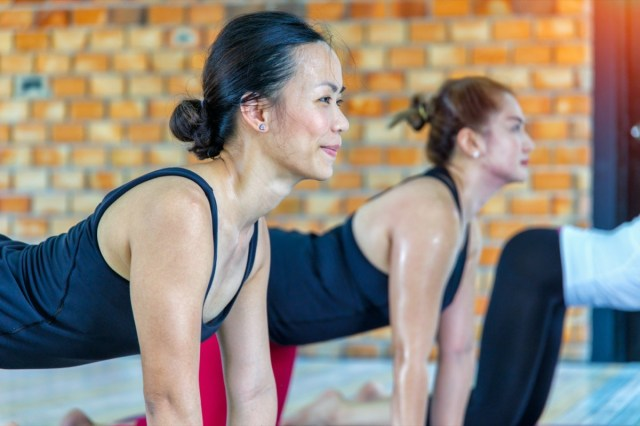 asian female group doing namaste yoga pose in row at the yoga class