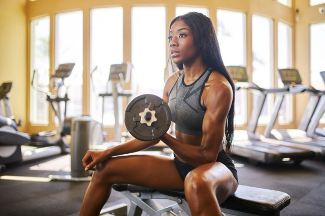 african american woman lifting weights in gym