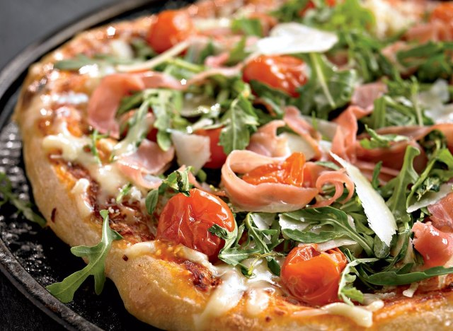 Healthy pizza with arugula, cherry tomatoes, and prosciutto