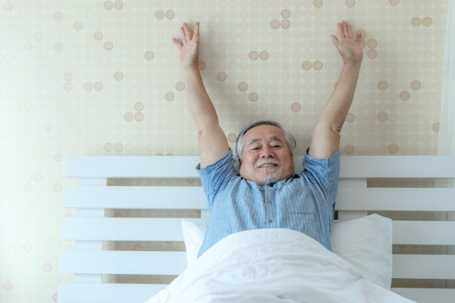 happy senior man good health wake up in the morning with joy on his bedroom