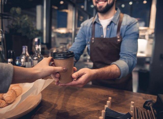 Customer handing coffee cup to barista