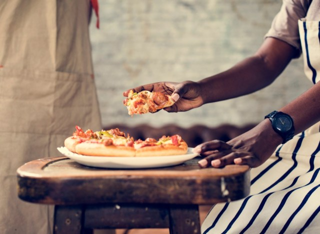 Man reaching for pizza