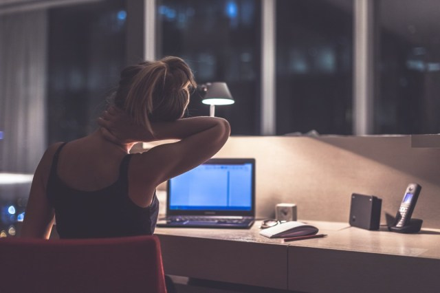 Young exhausted,depressed,concentrated woman sitting in her room or office with french windows in the dark at the lamp