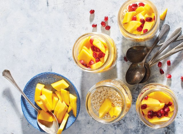 mango ginger overnight oat jars with spoons and pomegranate seeds