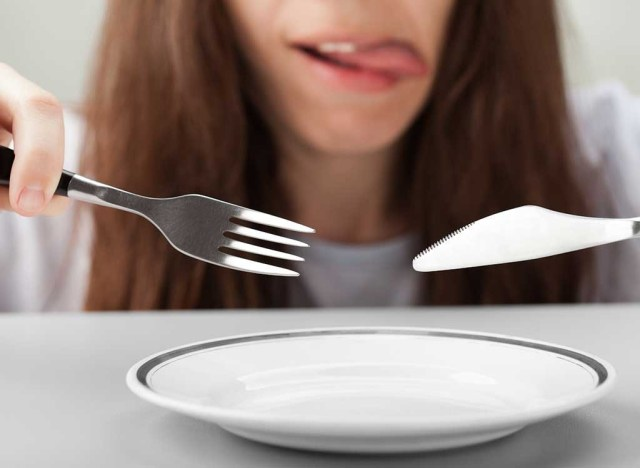 Hungry woman fork knife empty plate