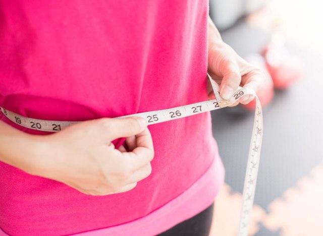 Woman measuring waistline