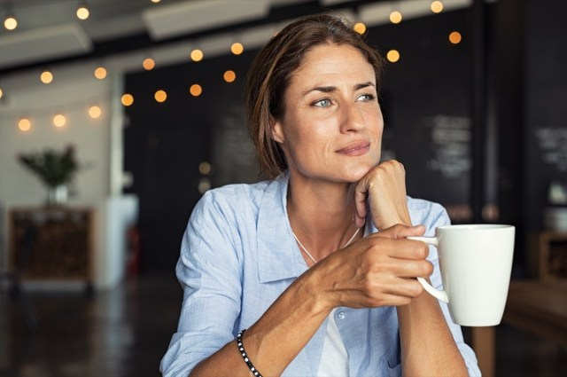 mature woman sitting in cafeteria holding coffee mug while looking away