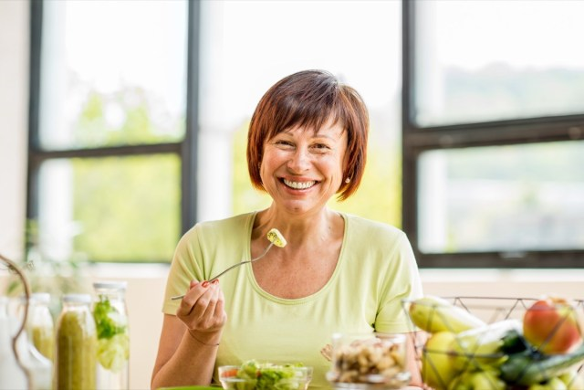 older woman with green healthy food on the table
