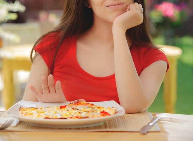 Woman pushing plate of pizza away to skip a meal