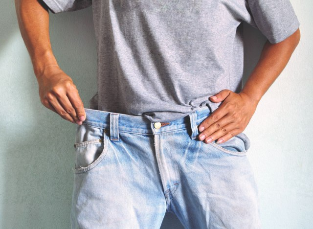 Man showing off weight loss wearing loose jeans