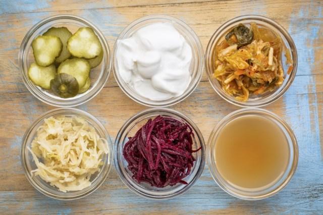glass bowls against grunge wood: cucumber pickles, coconut milk yogurt, kimchi, sauerkraut, red beets, apple cider vinegar