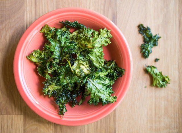 baked kale chips with olive oil and sea salt in an orange bowl
