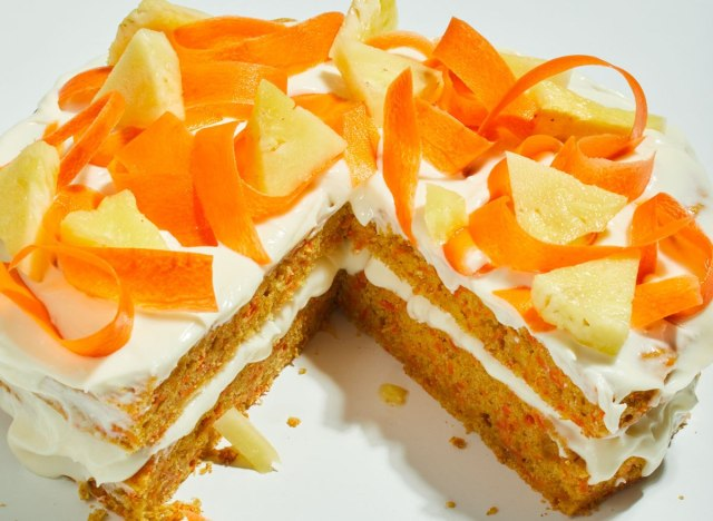 ginger carrot pineapple cake sliced with carrot and pineapple toppings on a white table