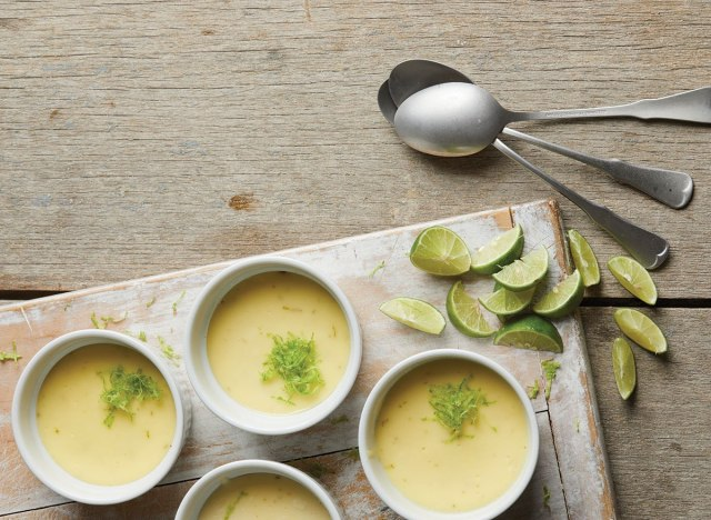 individual bowls of key lime cheesecake on serving tray with lime slices and spoons