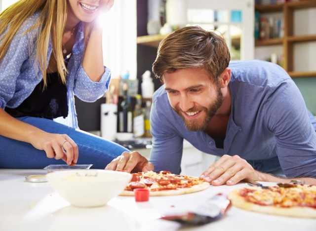 Couple cooking pizza