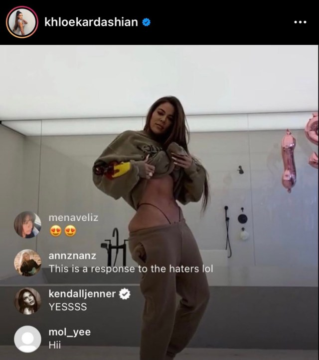 still from Instagram Live in in which Khloe Kardashian raises her sweatshirt to reveal her abs