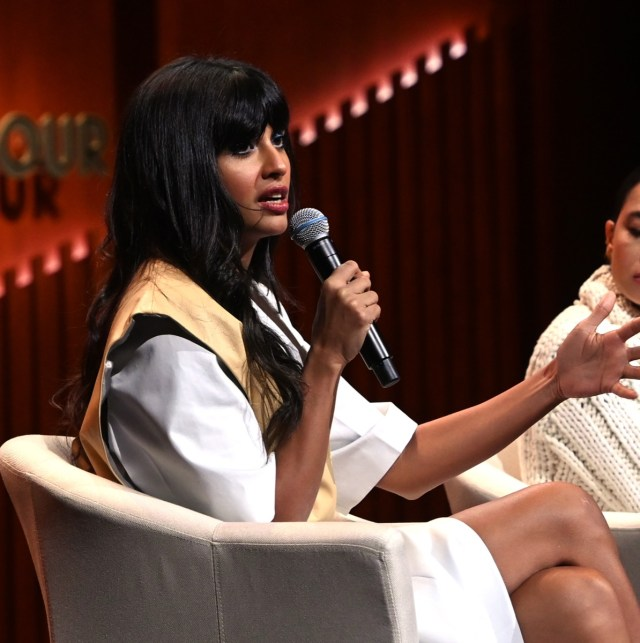 jameela jamil in white top and tan vest holding microphone while seated