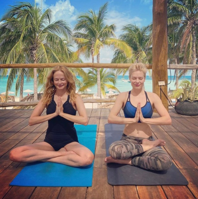 heather graham and a female friend meditating or doing yoga outdoors