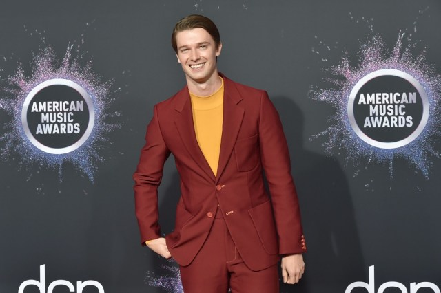 patrick schwarzenegger in red suit and yellow shirt on red carpet