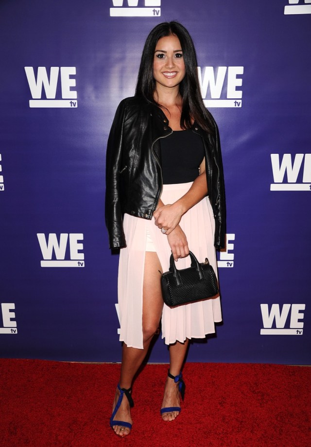 catherine giudici in black jacket and white skirt on red carpet