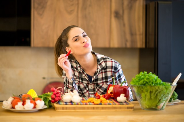Young woman in the kitchen eating slice of red pepper.