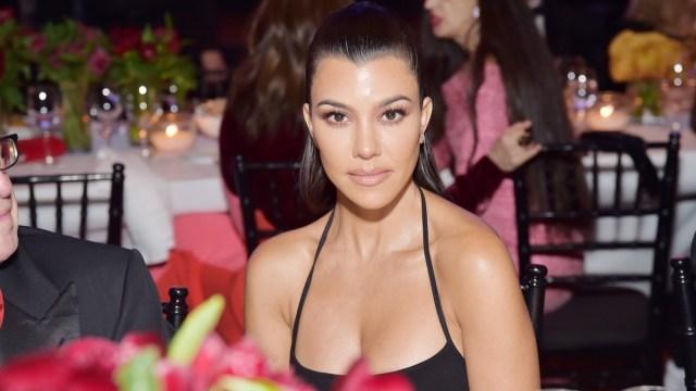 kourtney kardashian seated in black dress
