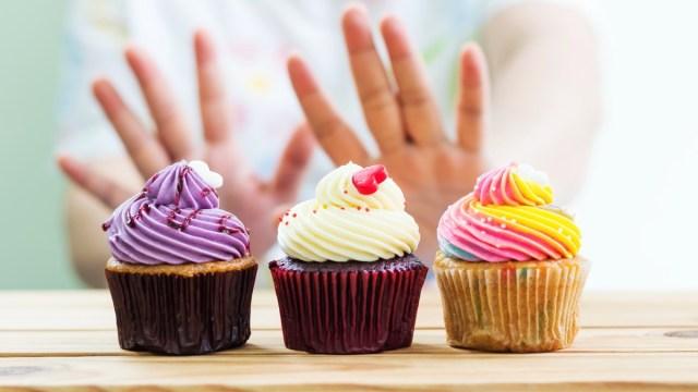 woman refusing cupcakes