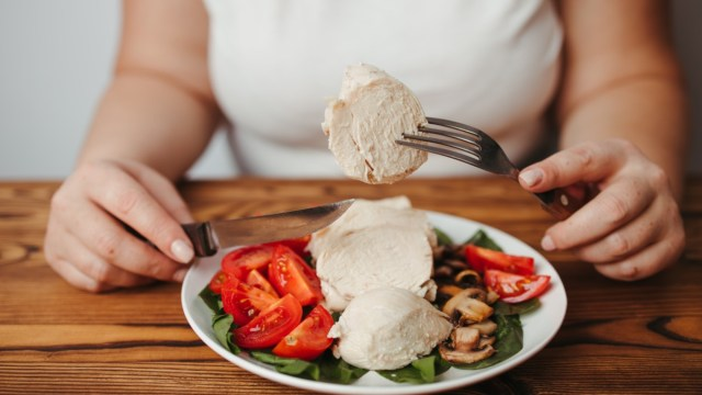 Woman eating baked chicken breasts with salad.