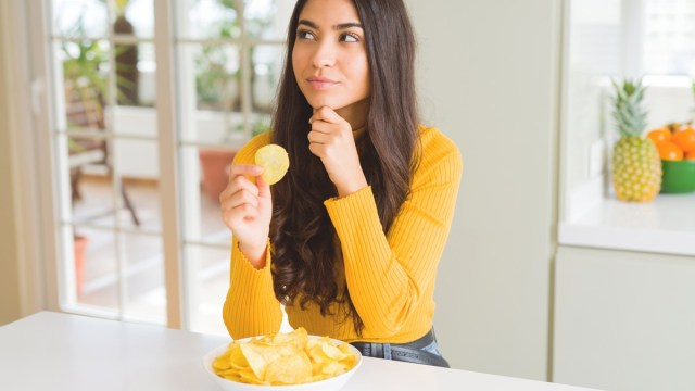 woman thinking about eating a potato chip and practicing mindful eating